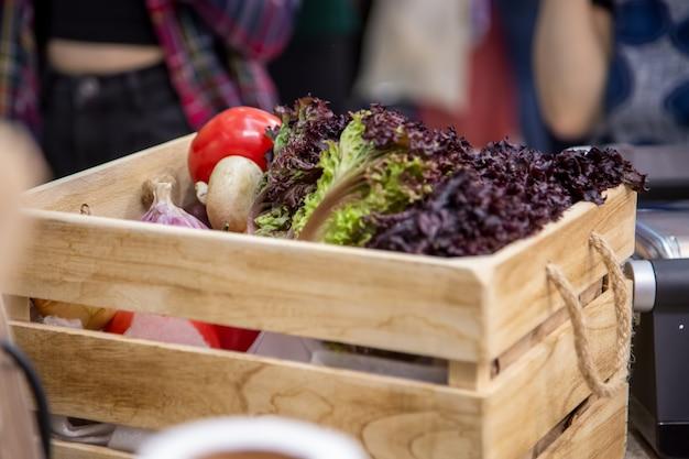 Close-up lght houten kist met set van verse biologische groenten knoflook, champignons, ui, tomaten, sla bladeren. concept van biologisch, bioproducten, bio-ecologie, zelf gekweekt, vegetariërs, fa