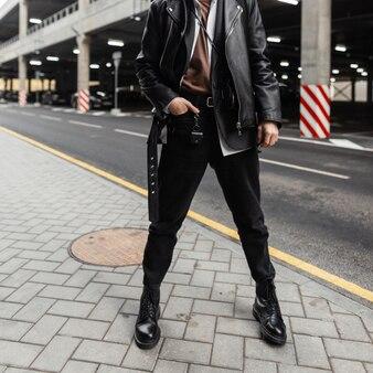 Close-up lichaam van een jonge man in een oversized stijlvol leren jack met een riem in een klassiek shirt in trendy jeans in coole seizoenslaarzen in de buurt van een weg in de stad. modieuze kerel. amerikaanse stijl.