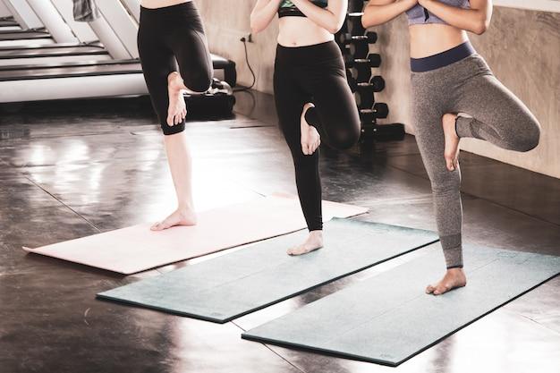 Close-up lichaam van vrouw doen yoga oefening samen in de sportschool.