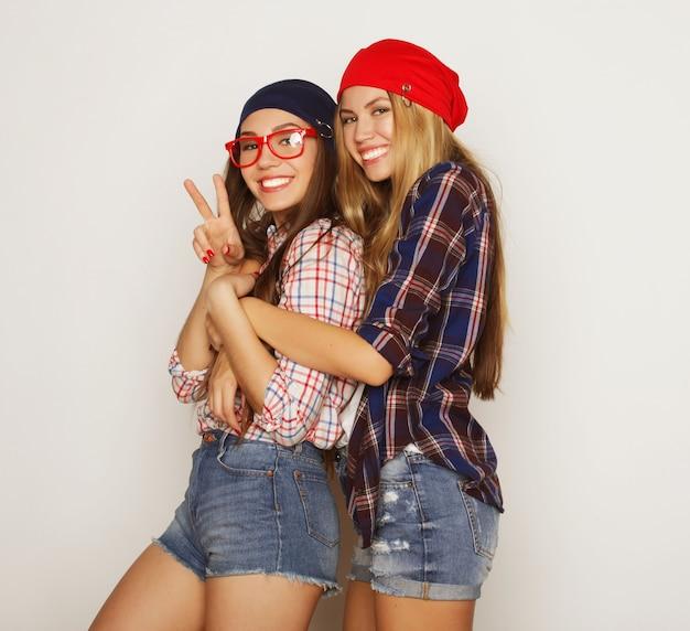 Close-up lifestyle portret van twee mooie tiener vriendinnen glimlachen en plezier hebben, hipster kleding, bril en hoeden dragen, positieve stemming.