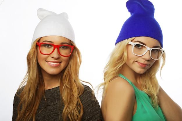 Close-up lifestyle portret van twee mooie tiener vriendinnen glimlachen en plezier hebben, hipster kleding, hoeden en glazen dragen, positieve stemming.
