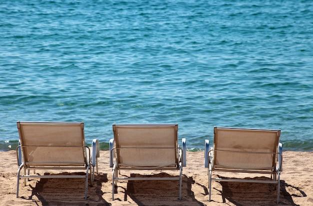 Close-up ligstoelen op de kust