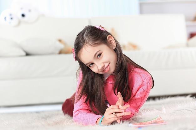 Close up.little meisje trekt liggend op de vloer in de kamer.