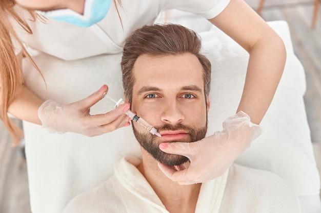 Close-up maakt mesotherapie-injecties voor baardman. behandeling van de man door een schoonheidsspecialiste voor haargroei.