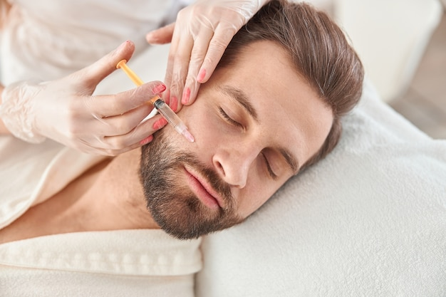 Close-up maakt mesotherapie-injecties voor jonge man. behandeling van de man door een schoonheidsspecialiste voor het aanhalen en gladstrijken van rimpels op de gezichtshuid.