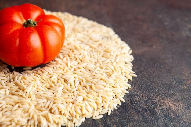 Close-up macaroni in de vorm van een cirkel met tomaat op hen op donkere gestructureerde achtergrond. horizontaal