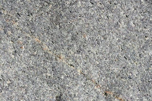 Close-up macro weergave van ruwe grijze stenen oppervlak. gedetailleerde aardachtergrond of patroontextuur die in natuurlijke omgeving wordt genomen. door de jaren heen verweerd, uniek en onnavolgbaar effect op structuurdesign.