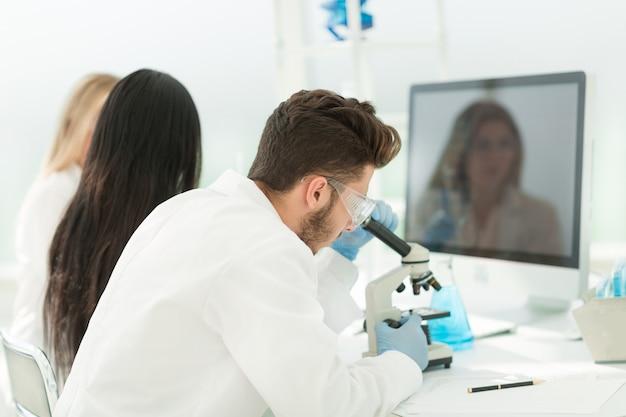 Close up.male wetenschapper zittend aan een lab tafel. wetenschap en gezondheid