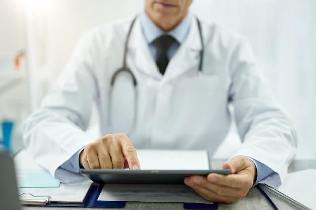 Close-up man arts in laboratoriumjas zittend aan tafel met documenten en surfen op het internet op elektronische pad-pc