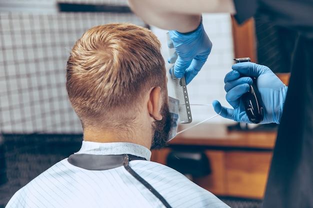Close-up man die haar laat knippen in de kapperszaak met een masker tijdens de pandemie van het coronavirus. professionele kapper die handschoenen draagt. covid-19, schoonheid, zelfzorg, stijl, gezondheidszorg en geneeskundeconcept.