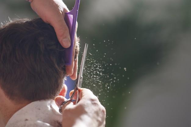 Close-up man die het haar van een jongen thuis knipt, moet je het haar van het kind bijwerken