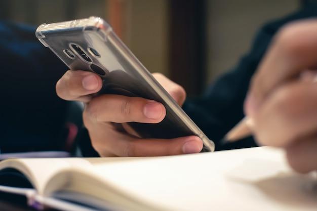 Close-up man die mobiele telefoon vasthoudt en gebruikt met een andere hand die de pen op notebook houdt.