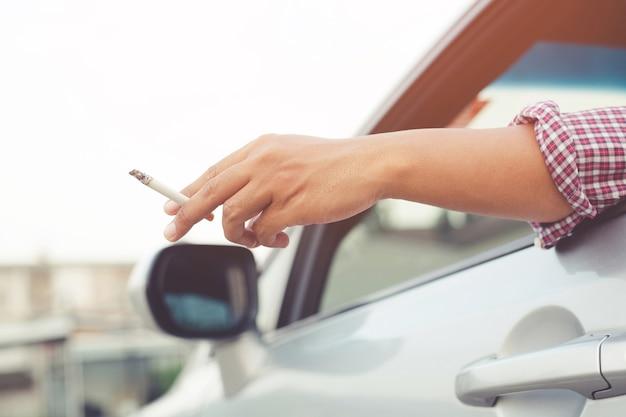 Close-up man hand houden roken van een sigaret in auto tijdens het rijden reizen