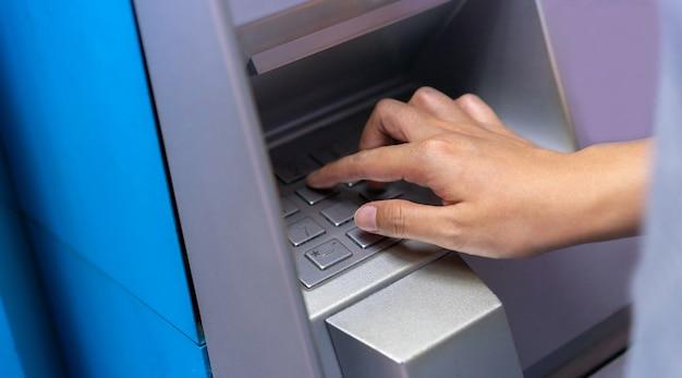 Close-up man hand te drukken op atm-machine voor ontgrendelen wachtwoord of geld tellen