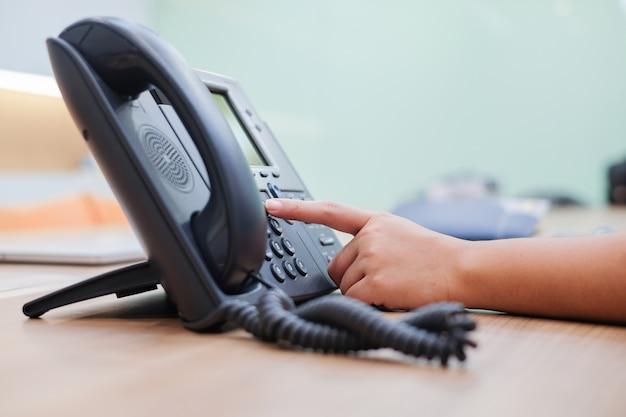 Close-up man hand wijzen proberen te drukken knop nummer op telefoon bureau