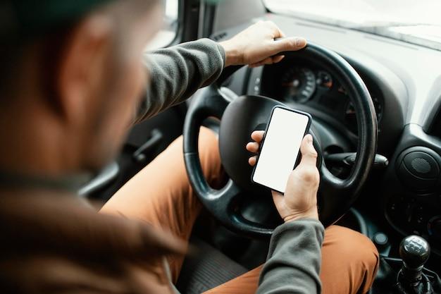 Close-up man in de auto met mobiel