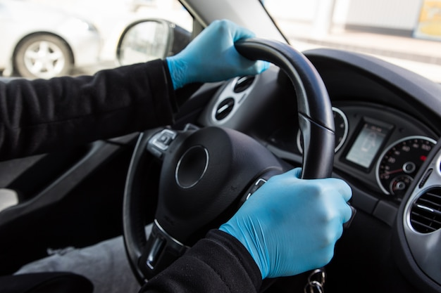 Close-up man in een blauwe handschoenen zit aan het stuur van een auto tijdens een epidemie