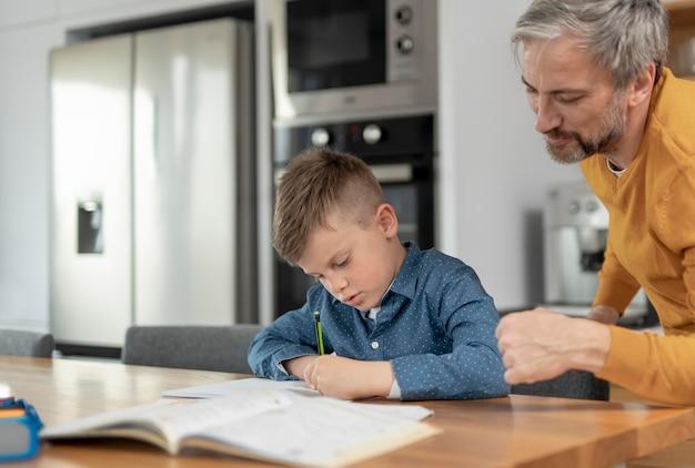 Close-up man kind helpen met huiswerk