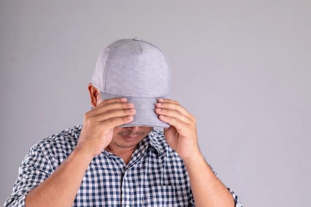 Close-up man met grijze pet en zijn gezicht verborgen