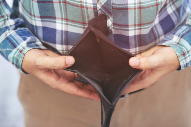 Close-up man persoon met een lege portemonnee, geen geld, faillissement