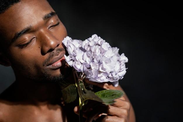 Close-up man ruikende bloemen