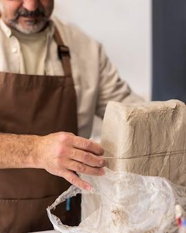 Close-up man snijden klei