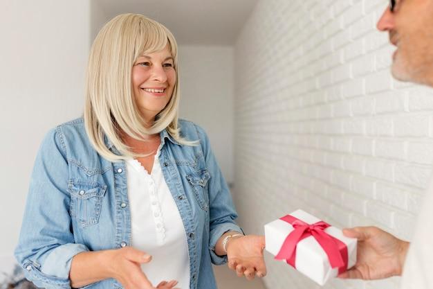 Close-up man verrassende vrouw met cadeau