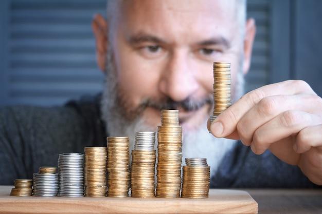 Close-up man verzamelt kolommen van veelkleurige munten van toenemende hoogte.