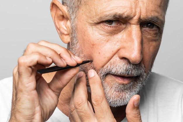 Close-up man zijn gezicht plukken