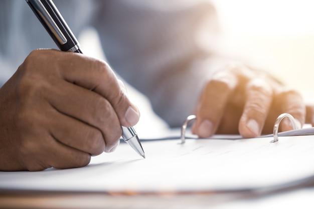 Close-up mannelijk hoger hand het schrijven het concept van het contractdocument