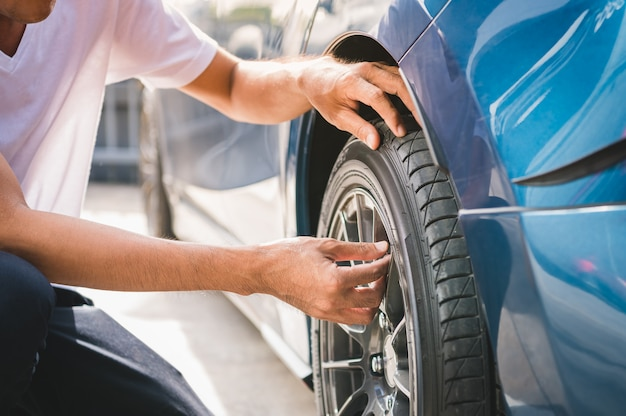 Close-up mannelijke automobieltechnicus die de klep van de bandklepstikstof voor bandinflatie verwijderen