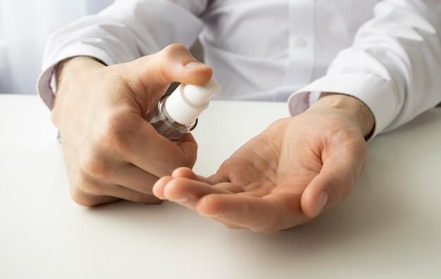 Close-up mannelijke behandelen hand met antiseptische maken desinfecterende coronavirusbescherming. man arm met procesveiligheid tegen bacteriële infectie met ontsmettingsmiddel antiseptische gel alternatief voor wassen met zeep