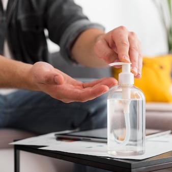 Close-up mannelijke desinfecterende handen thuis