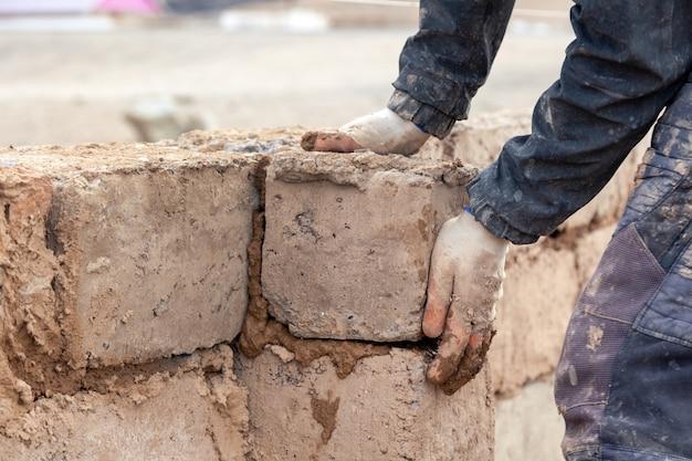 Close-up mannelijke handen bouwen muur van onvoltooide huis uit baksteen