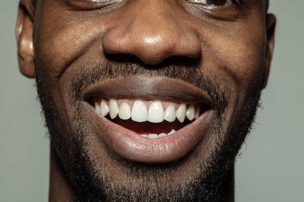 Close-up mannelijke mond met een grote glimlach en gezonde tanden. cosmetologie, tandheelkunde en schoonheidsverzorging, emoties