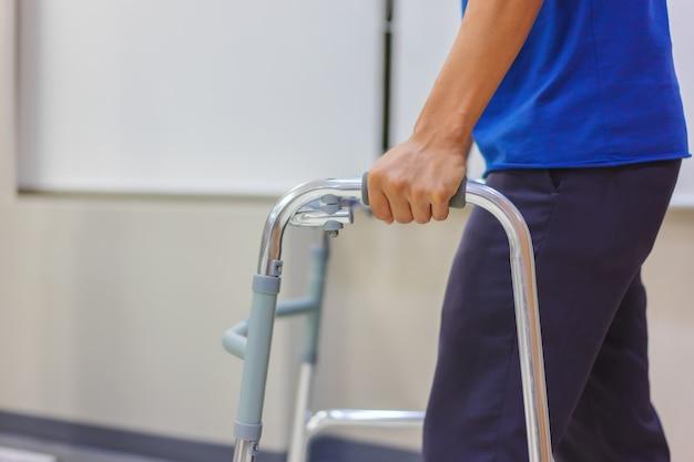 Close-up, mannelijke patiënt op middelbare leeftijd gebruikt wandelaars om te wandelen na een operatie.