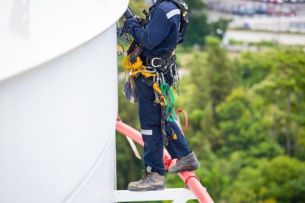 Close-up mannelijke werknemers controleren apparatuur touw naar beneden dak tank touwtoegang inspectie van dikte schaalplaat opslagtank gasveiligheidswerk op hoogte.