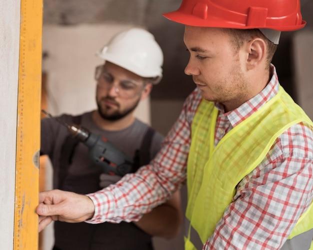 Close-up mannen werken samen met boor