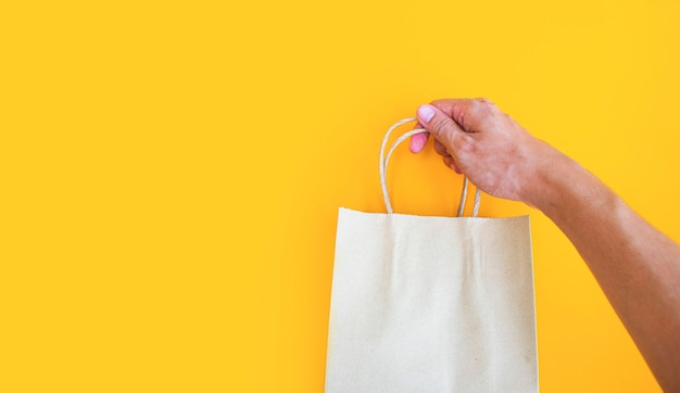 Close-up mannenhand holing lege papieren zak voor afhaalmaaltijden op gele achtergrond
