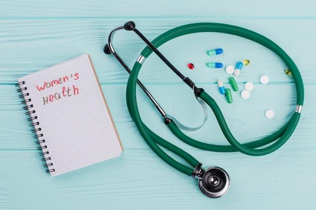 Close-up medische stethoscoop en drug pillen liggend op blauwe achtergrond. lees vrouwengezondheid op kladblok.