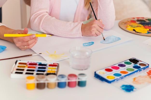 Close-up meisje en vrouw samen schilderen