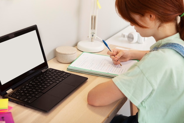 Close-up meisje in online klas aantekeningen maken