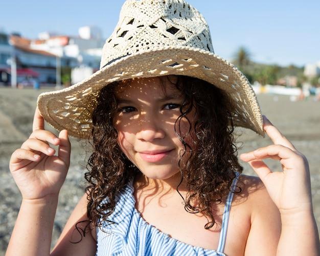 Close-up meisje met hoed op strand Gratis Foto