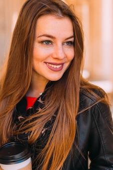 Close-up meisje met sproeten in stijlvolle kleding met een kopje koffie
