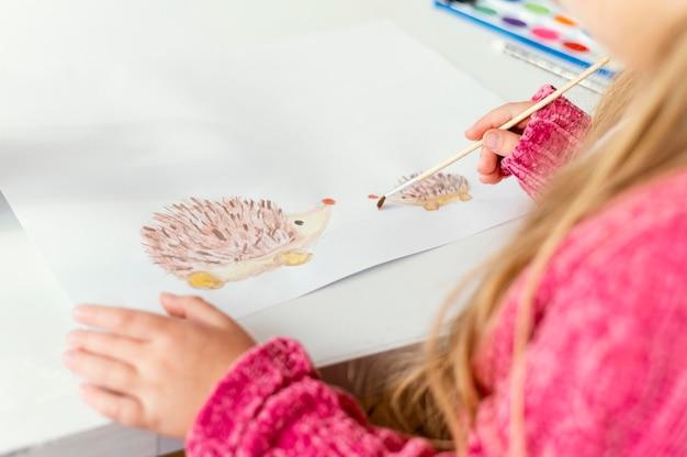 Close-up meisje schilderen binnenshuis met borstel