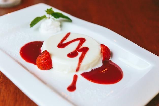 Close-up melkpudding geserveerd met aardbeiensaus, slagroom, gesneden verse aardbeien en munt.