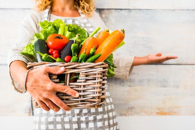 Close-up met een blanke vrouw die een emmer vol gekleurde en verse seizoensgroenten neemt voor een gezonde en natuurlijke levensstijl