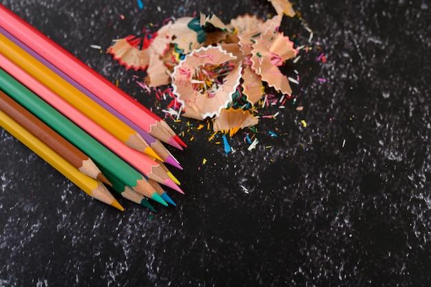 Close-up met kleurpotloden en spaanders op vlakke cementvloer.
