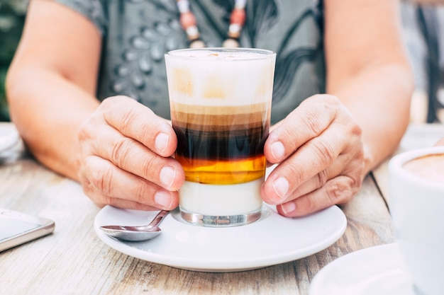 Close-up met oude vrouwelijke handen met een kopje meerkleurige koffie voor het ontbijt aan de bar - houten tafel en helder beeld - drank- en drankconcept voor mensen