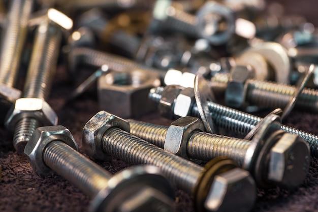Close-up metalen chromen bouten en moeren in een chaotische volgorde. reparatie- en reserveonderdelenconcept